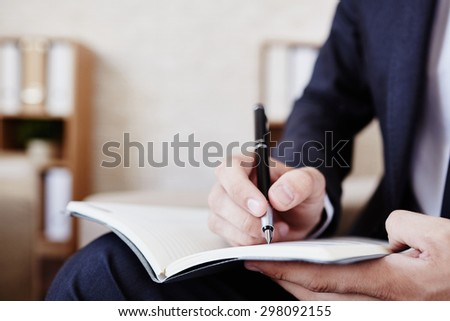 Male employee making notes in notepad
