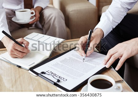 Male employee reading contract while his colleague making notes - stock photo