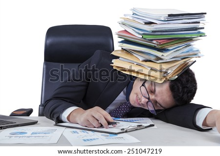 Male employee sleeping on desk with paperworks on his head, isolated on white background - stock photo