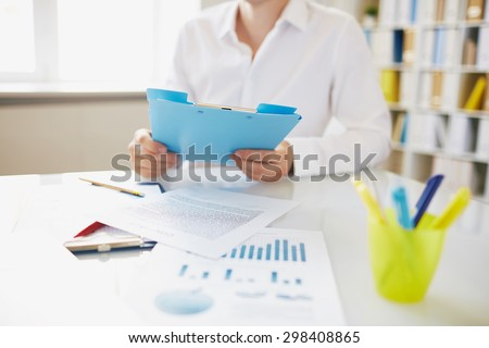 Male employee with clipboard sitting at workplace - stock photo