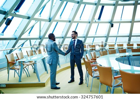 Male employees handshaking in conference hall - stock photo