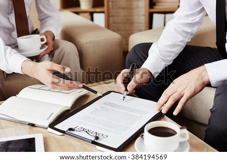 Male employees pointing at contract while discussing terms - stock photo
