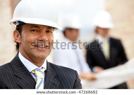 Male engineer at a construction site smiling - stock photo