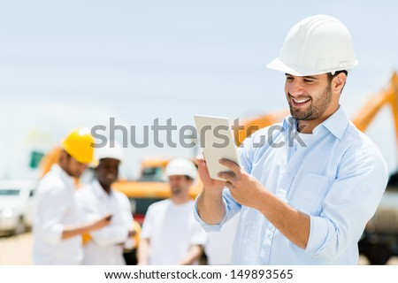 Male engineer at a construction site with a tablet computer  - stock photo