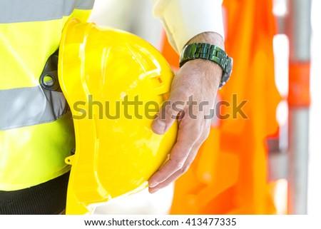 Male engineer hand holding yellow helmet - stock photo
