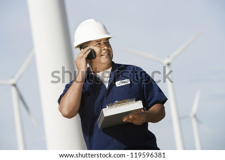 Male engineer on call holding clipboard and looking away at wind farms
