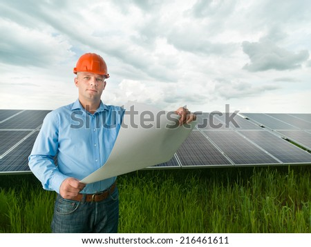 male engineer standing in solar panel station, holding blueprints - stock photo