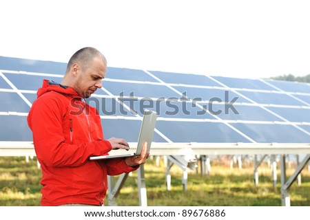 Male engineer using laptop, solar panels in background - stock photo