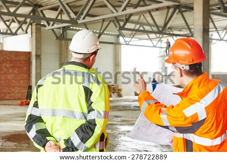 male engineers construction foreman managers outdoors at building site with blueprints - stock photo