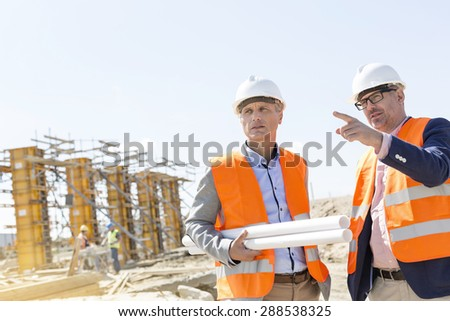Male engineers discussing at construction site against clear sky - stock photo