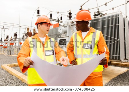 male engineers discussing blueprint at electrical substation - stock photo