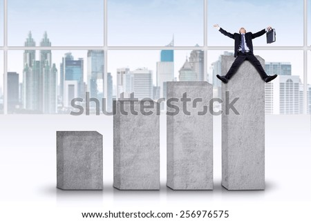 Male entrepreneur celebrate his success on the business chart, shot in the office - stock photo