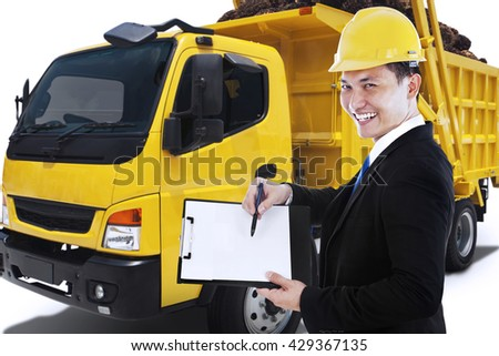 Male entrepreneur holding a clipboard while smiling at the camera with a delivery truck carrying palm fruit - stock photo