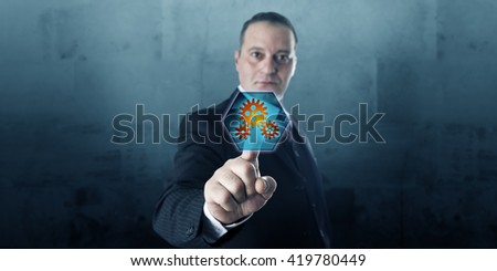 Male entrepreneur is pressing a hexagonal push button displaying three gear wheels. The virtual icon is lighting up. Business concept and technology metaphor for process activation in cyberspace. - stock photo