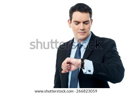 Male entrepreneur looking time on his wrist watch - stock photo