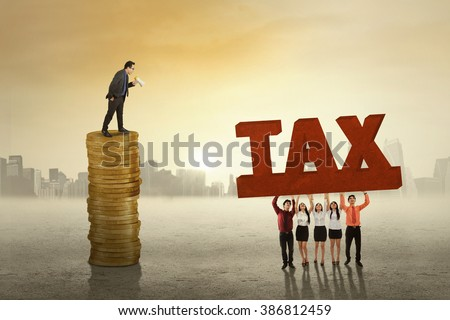 Male entrepreneur standing on the golden coins and give command on his workers to lift a tax word
