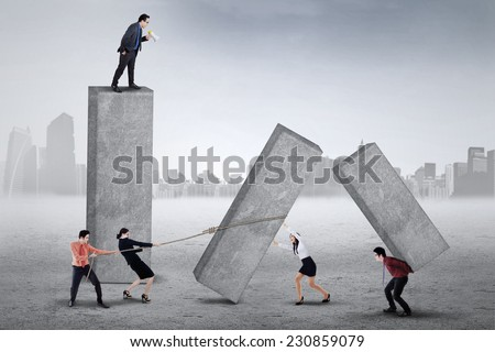 Male entrepreneur standing on the top and yelling to his workers for working harder - stock photo