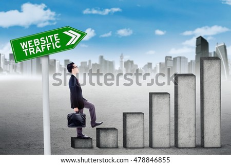 Male entrepreneur walking on the rising graph of website traffic, shot outdoors