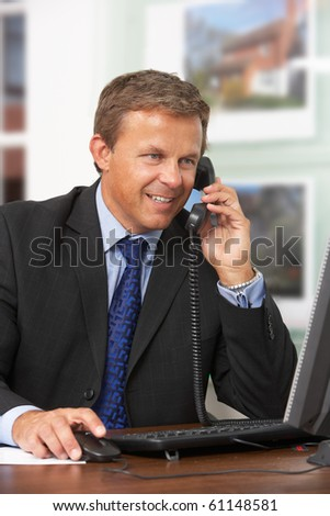 Male Estate Agent Talking On Phone At Desk - stock photo