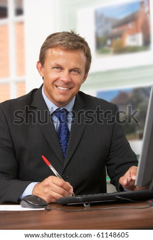 Male Estate Agent Working At Desk - stock photo