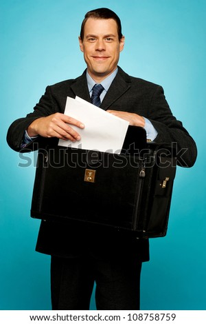 Male executive arranging paper works and keeping them safely in bag - stock photo