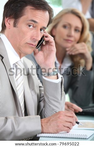 Male executive on cellphone during meeting - stock photo