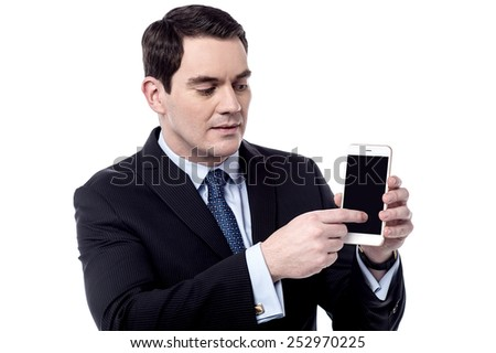 Male executive showing something on his cell phone - stock photo