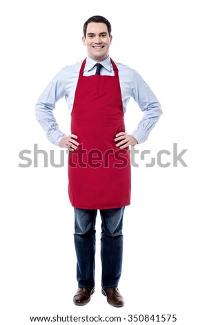 Male executive wearing apron and posing with hands on waist - stock photo