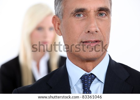 Male executive with female colleague out of focus in the background - stock photo