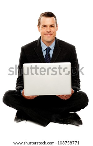 Male executive with laptop sitting on the floor. Legs crossed. Studio shot - stock photo