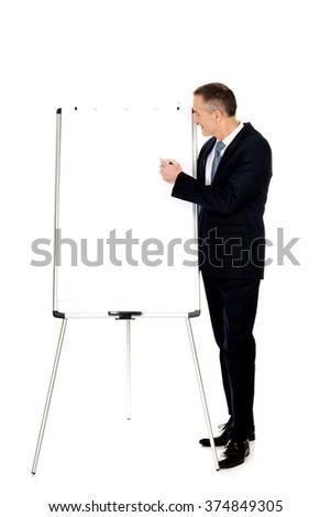 Male executive writing on a flipchart - stock photo
