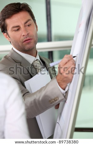 Male executive writing on a full size flipchart - stock photo