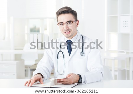 Male experienced doctor in office checking visit in his calendar - stock photo