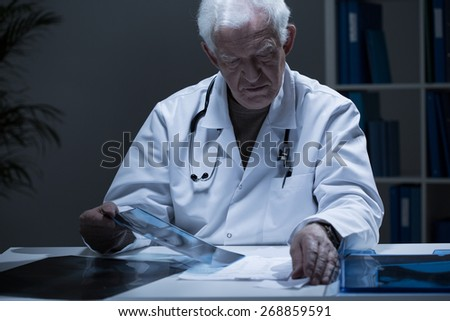 Male experienced doctor looking at x-ray image - stock photo