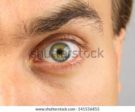 male eye, looking menacingly, raised eyebrow - stock photo