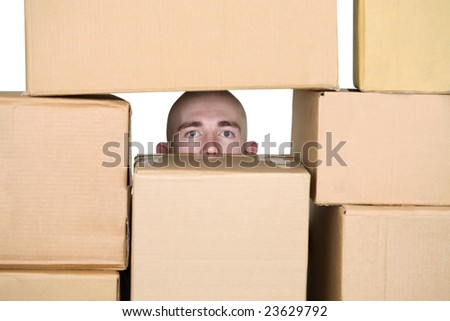 Male face in pile of cardboard boxes on a white - stock photo