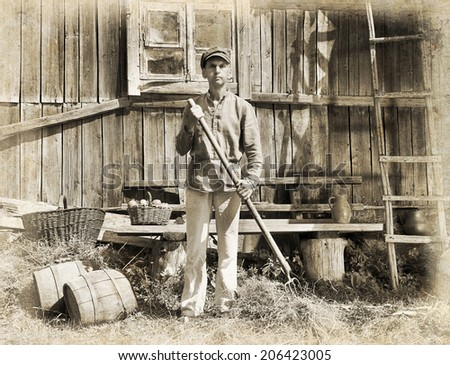 Male farmer holding a pitchfork. Intentional 1900's style post processing emulation.  - stock photo