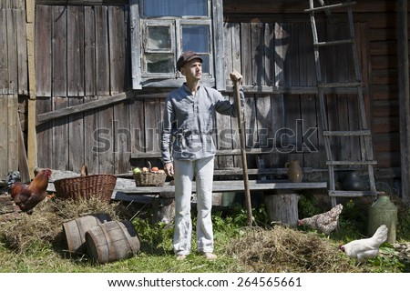 Male farmer holding a pitchfork, standing in front of wooden stable while some hens grazing in the grass - stock photo