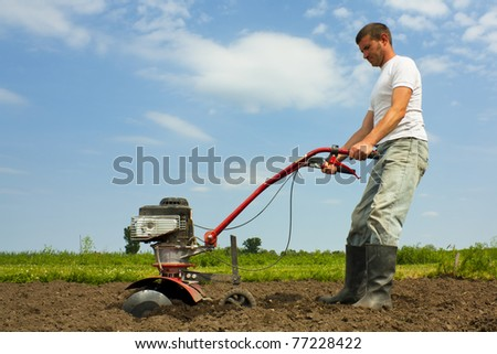 Male farmer using a cultivator or rotovator to till soil - stock photo
