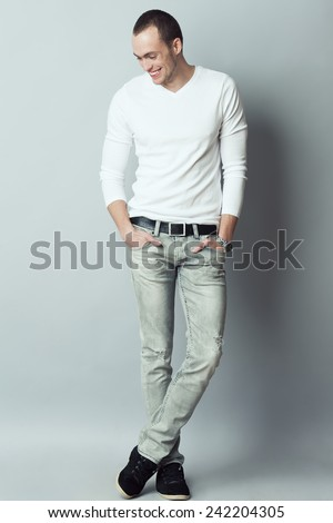Male fashion concept. Fashionable young man with haircut wearing trendy clothes, footwear & posing over gray background. Perfect smile & skin. Hands in pockets, crossed legs. Street style. Studio shot - stock photo