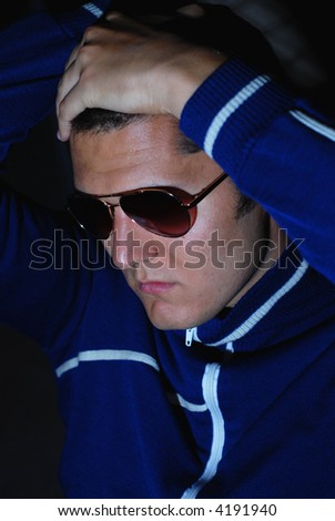 Male fashion model in aviator sunglasses and trendy sweater - stock photo