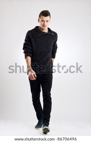 male fashion model wearing wool sweater, walking towards camera - stock photo