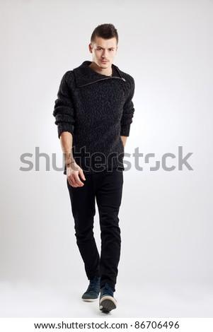 male fashion model wearing wool sweater, walking towards camera - stock photo