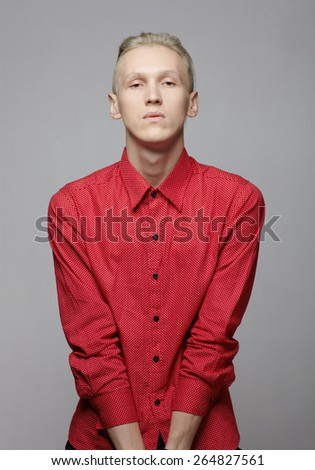 Male fashion model with blonde hair style against gray background in studio - stock photo
