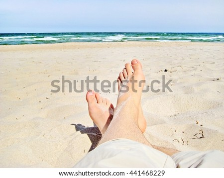 male feet at the sandy beach - legs with short trousers