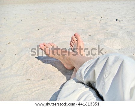male feet at the sandy beach - legs with short trousers - stock photo