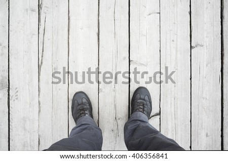 Male feet in leather shoes stand on white wooden floor, first person view - stock photo