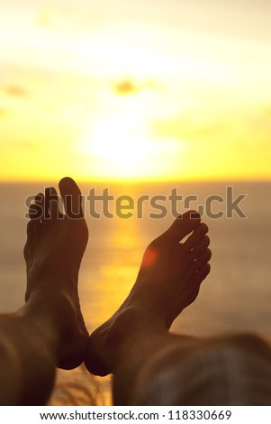 Male feet in relaxed pose silhouetted by sunset over ocean - stock photo