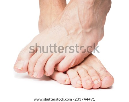Male feet one over the other isolated towards white - stock photo