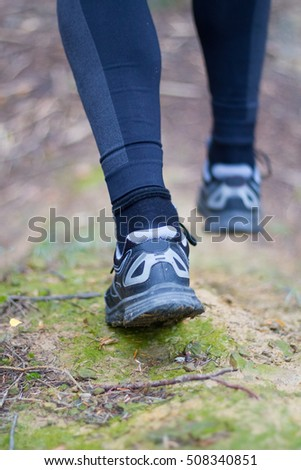 Male feet running on trail in mountains